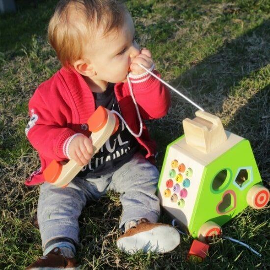 Axel avec son téléphone post-millénium : sélection des jouets en bois Petits Chats