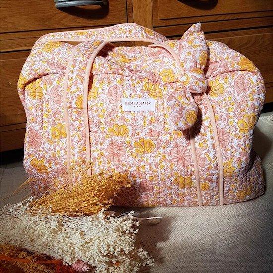 La boutique Le coffre aux merveilles propose un sac à langer poudré